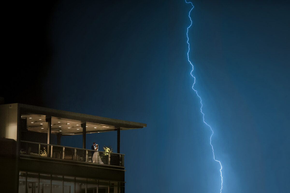 Newly married couple embraces on the balcony of their wedding reception in Greenville SC during a lightning storm.
