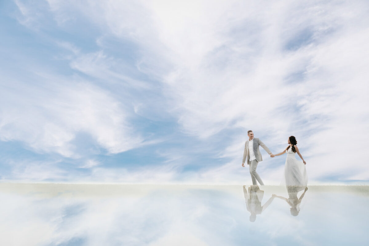 Newlyweds hold hands and walk through a sky filled with clouds