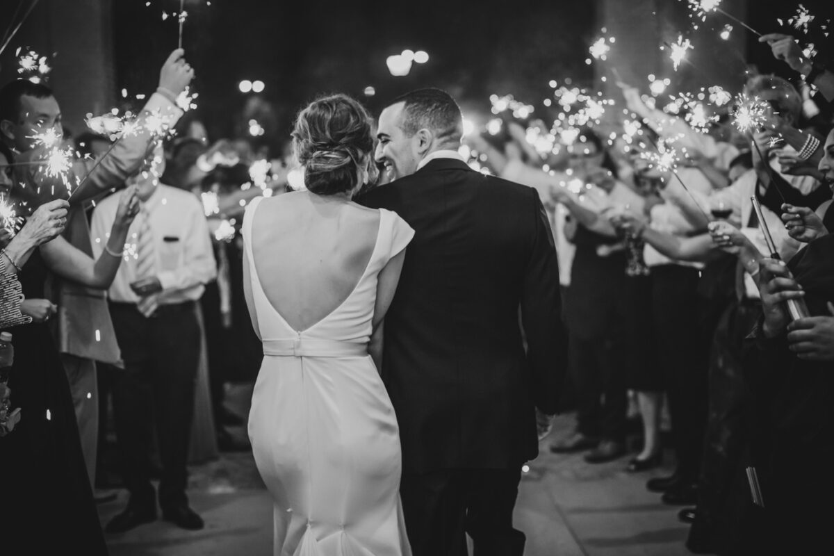 Husband and wife leave their reception to a sparkler exit from the Greenville Country Club.