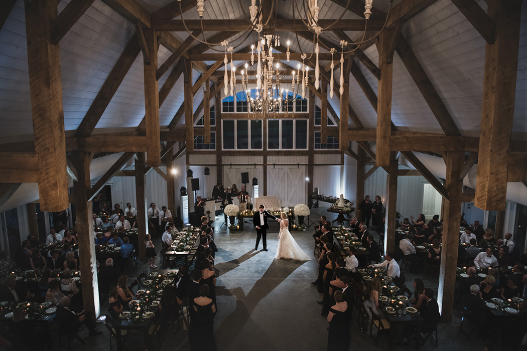 A bride and groom dance at their barn wedding reception.