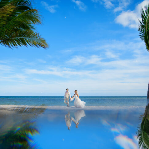 A soon-to-be married couple walks down the beach between two palm trees.