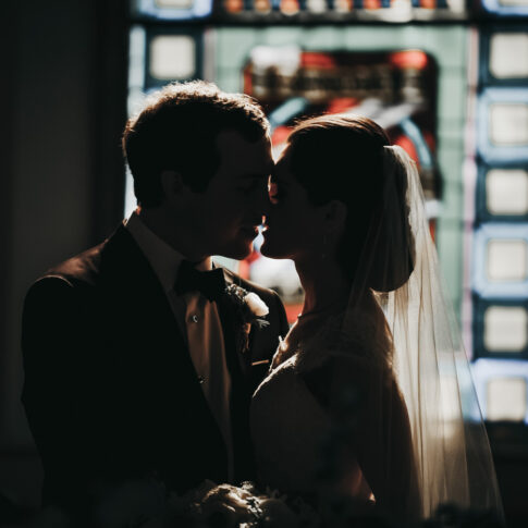 Sun shines through stained glass window of a church onto a bride and groom and their impending kiss.