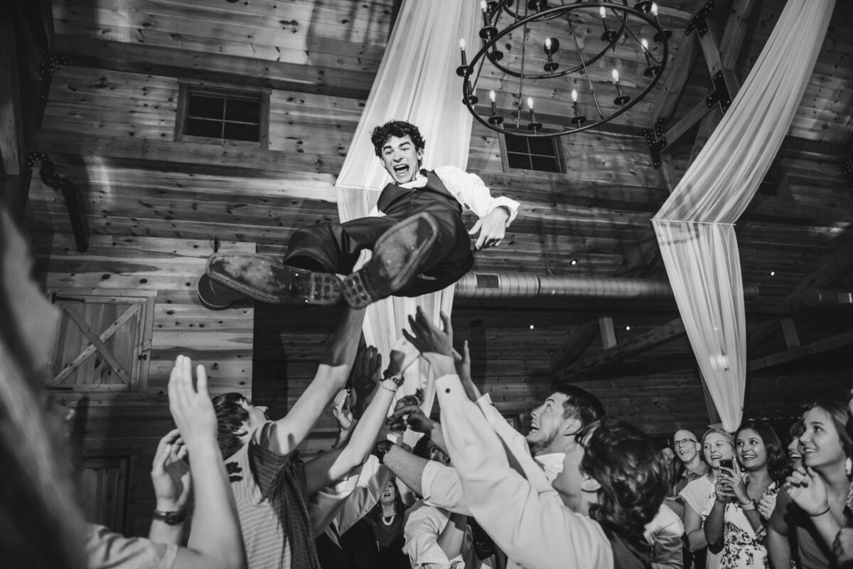 Groomsmen throw the groom high in the air at a reception celebration.
