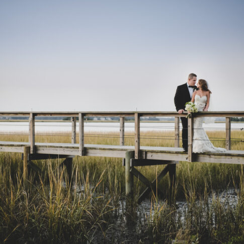 A bride and groom embrace in a stunning sunset overlooking the marsh and river in South Carolina.