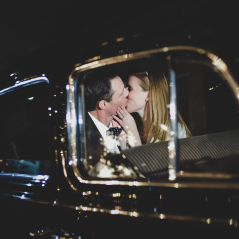 A bride and groom sneak a kiss in the back of their getaway car as they are leaving their wedding reception.