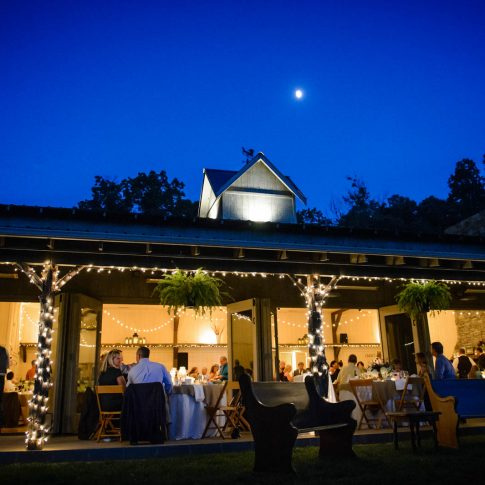 The moon rises into the deep blue evening sky above the farm in Candler North Carolina. Inside the pavilion the newlyweds and their friends and family celebrate on the cool September evening. I love the way the tiny white Christmas lights wrapped around the posts of the porch…glow adds to the warm ambience. On the far left side of the image you can see the band on the porch. It's the same band Ally and Barry Saul performing on their very first date. The entire wedding day was full of emotional and personal details like that, thanks to the hard work of planner Amanda Cox.
