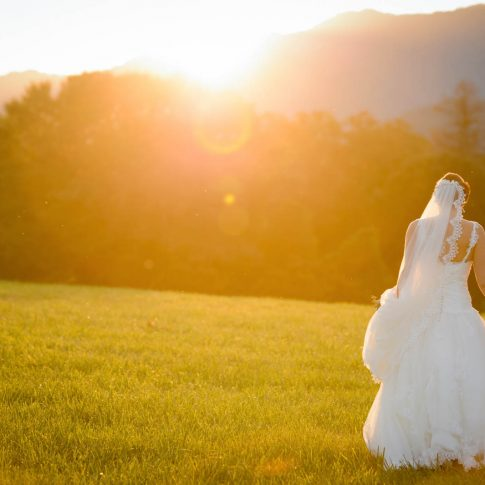A bride and groom hold hands and walk away towards the setting sun over the NC mountains.