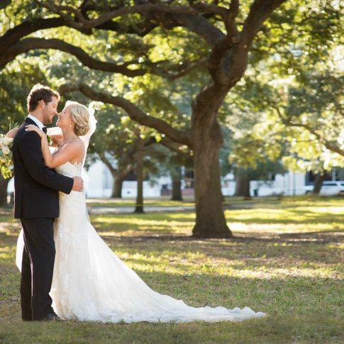 A bride hugs her groom under a canopy of back lit oak trees.