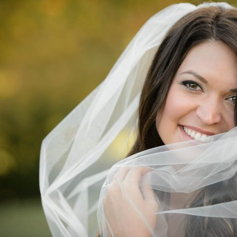 A bride smiles into the camera as she pulls her tulle veil across her.