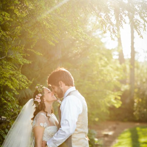 Moments before a kiss, newlyweds embrace outdoors under a warm ray of sunshine.