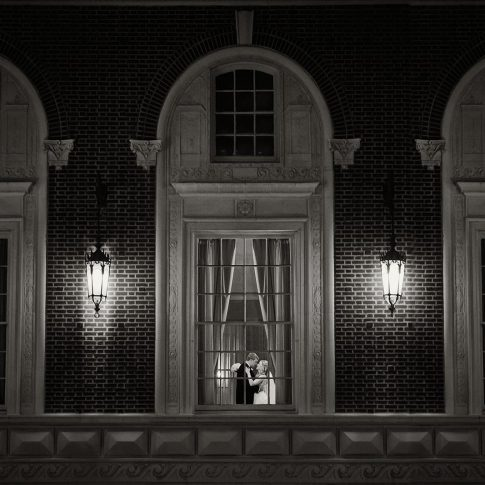 Photographed outside the Westin Poinsett Ballroom, looking through the window to newlyweds hugging.