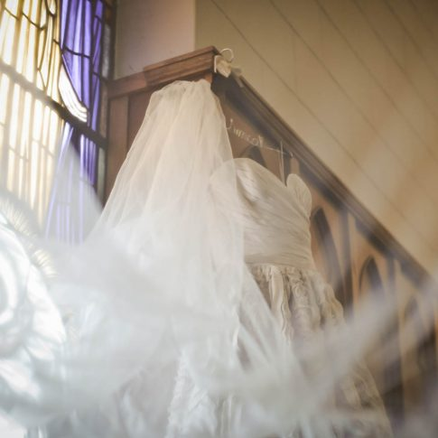 A wedding dress hangs in preparation for the big day on the edge of the wooden detail of the sanctuary of Bethel United Methodist Church in Spartanburg, SC.
