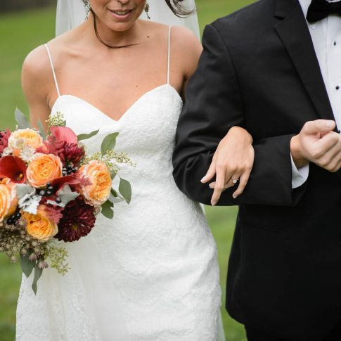A quick detail shot showcasing the warm summery floral arrangement and the pristine white lace of the wedding gown.