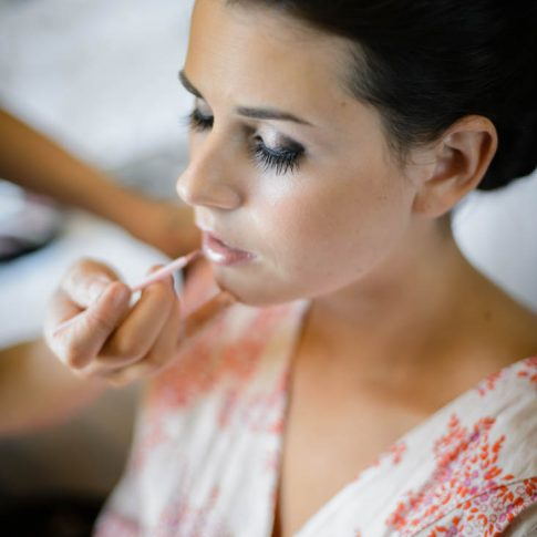 A thin layer of lipgloss is applied to the lips of the bride as she gets ready for the upcoming ceremony.