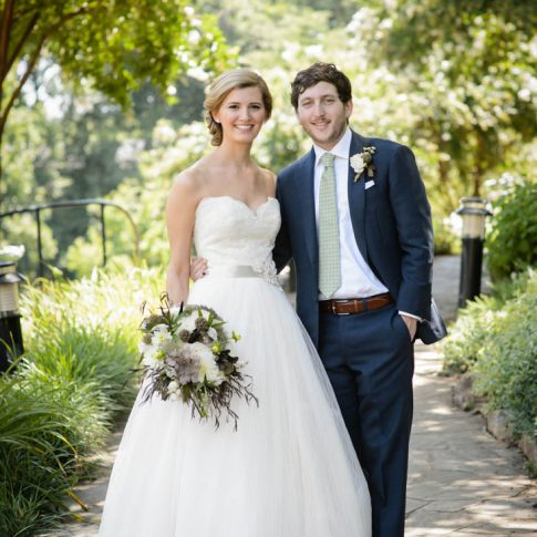 A bride and groom pause and smile on the pathway of Falls Park in downtown Greenville, SC.