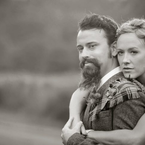 A bride and her groom, dressed in traditional Scottish apparel, embrace and gaze into the distance.