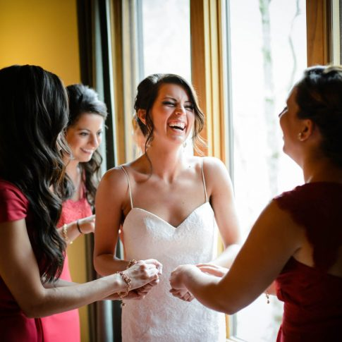 The bride grasps the hands of her bridesmaids in laughter moments before the commencement of the ceremony.