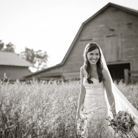 The bride lifts up the hem of her gown and smiles as she makes her way through a field outside of the barn where their upcoming nuptials will take place.