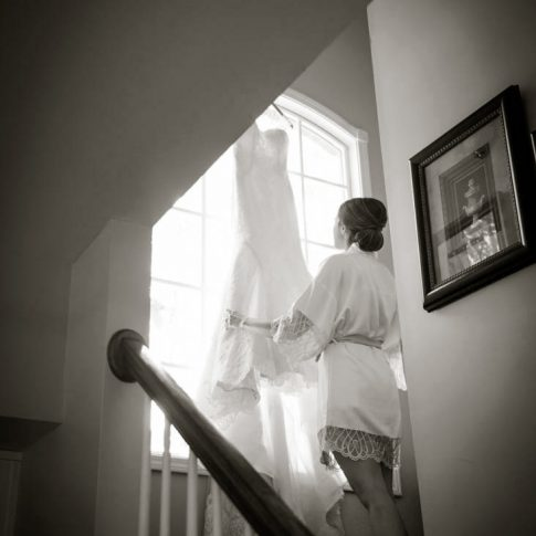 A bride carefully adjusts her wedding gown as it hangs from the windowsill as she is getting ready for her wedding ceremony.