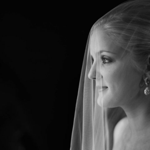 As a tulle bridal veil cascades over the face of the bride, she softly stares into the distance during a bridal photo session.