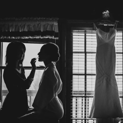 The silhouette of the bride getting ready is perfectly captured as her dress hangs from the window beside her.
