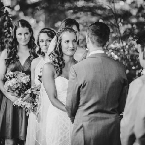 A bride lovingly admires her soon-to-be husband and begins to tear up during an outdoor wedding ceremony.