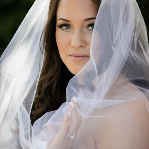 A bride gazes into the camera and gracefully cradles her veil during her bridal portrait session.