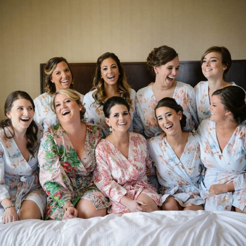 Bridesmaids join the bride in kneeling on the bed of the room they are getting ready for the wedding in and share a moment of laughter.