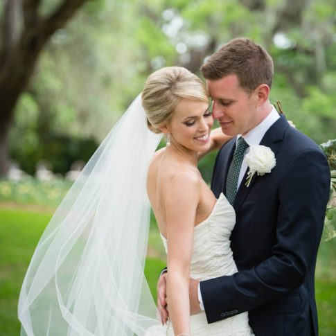 A groom lovingly gazes at his bride while she holds her veil from the wind at Brookgreen Gardens.