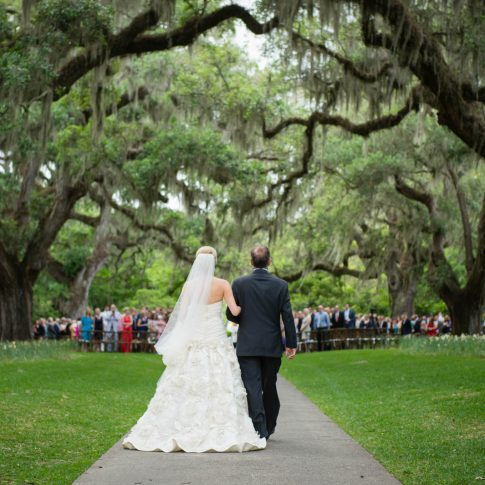 A bride, being escorted on the arm of her father, approaches the altar during a ceremony at Brookgreen Gardens.