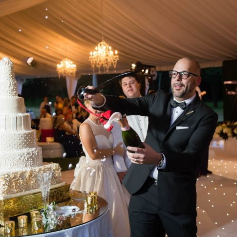 A groomsman expertly pops the bottle of champagne with a saber in preparation for a celebratory toast of the new couple.