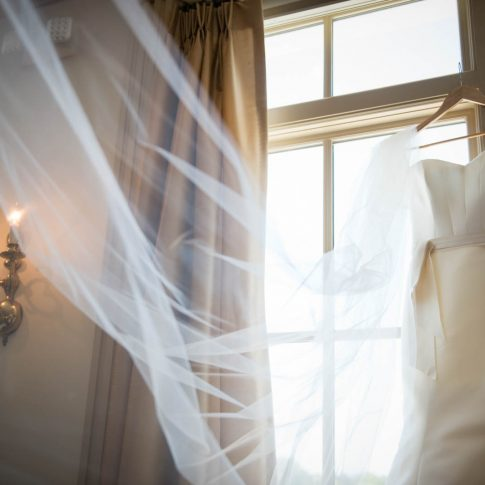 The wedding dress hangs elegantly on the windowsill of the window of the venue, the Charleston Country Club, as the veil gracefully cascades down.