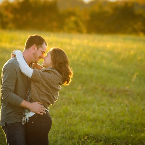 A jovial engaged couple embraces in the middle of a serene field and smiles in anticipation of a kiss.