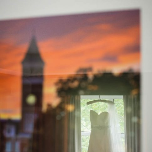 Reflecting in a framed photo of Tillman Hall at Clemson University, the brides alma mater, her wedding dress hangs softly on the window frame.