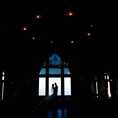 A bride and groom share an intimate gaze in the silhouette of the windows of their venue, The Cliffs at Glassy Chapel.