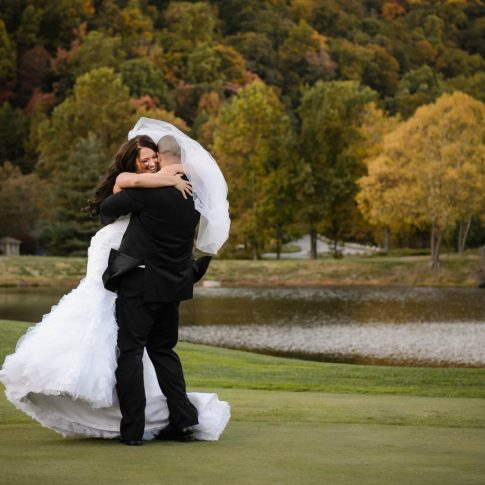 A bride joyfully embraces her new husband while out on the golf course of the venue, the Cliffs at Glassy Mountain.