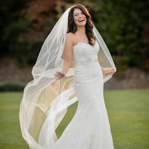 A bride laughs as she holds her veil back from the oncoming wind as she poses on the golf course of the beautiful Cliffs at Glassy Mountain.