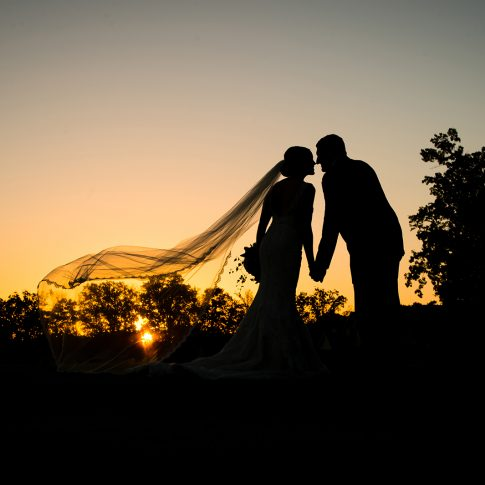 Silhouette photograph of a bride and groom at sunset.
