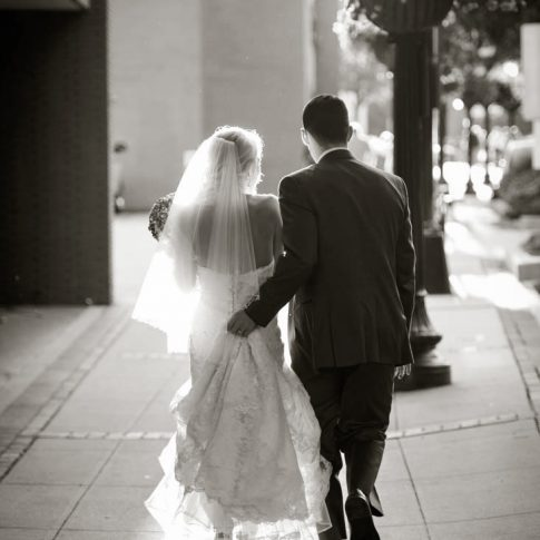 A groom assists his bride by holding up the hem of her dress as they walk down the street of downtown Greenville, SC.