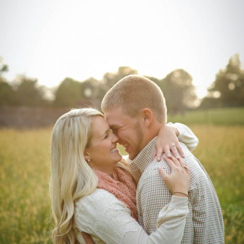 A happily engaged couple lovingly embraces in a sunny field.