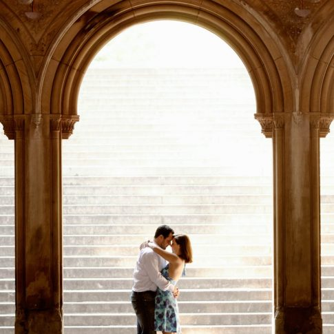 The soon-to-be-bride wraps her arms around her fiancé's neck underneath a magnificent archway during an engagement portrait session.