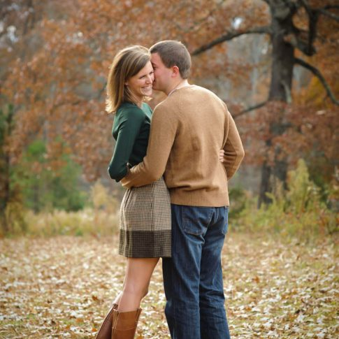 Fiance's happily lean in for a kiss on the cheek as they pose among the fallen fall leaves in Greenville, SC.