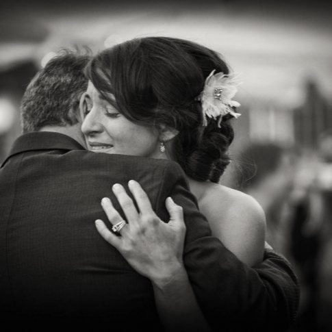 A daughter and father tearfully share a loving embrace on her wedding day.