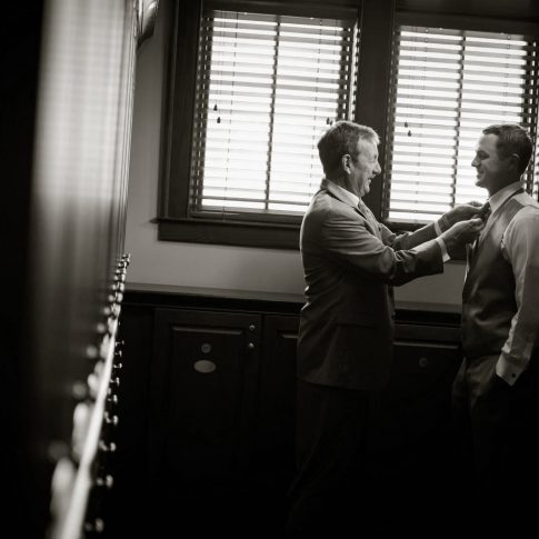 A father carefully adjusts his sons tie as they prepare for his upcoming wedding.