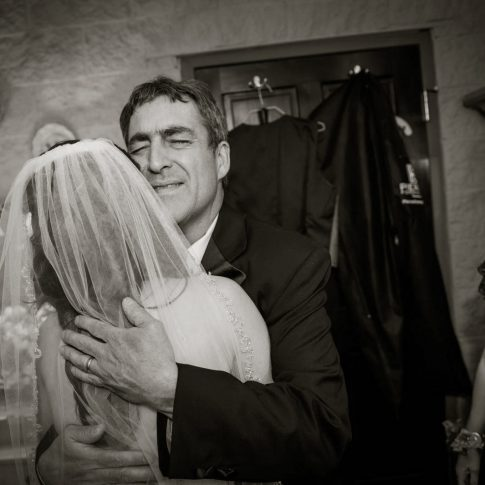 A father embraces his daughter on her wedding day as her mother looks on lovingly to this touching moment.
