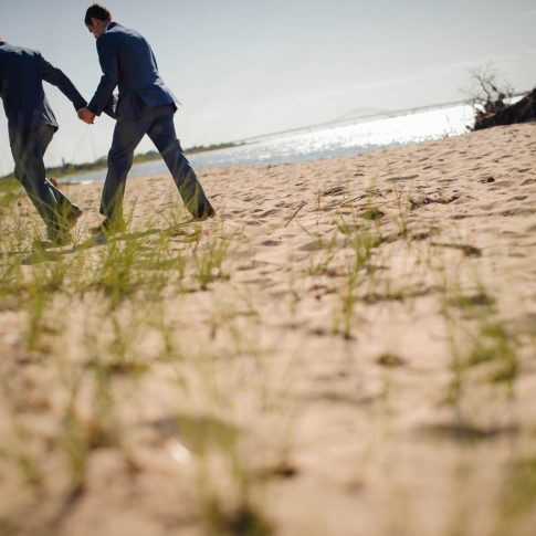 The happy new grooms walk across the beautiful beach of Fire Island shortly after their ceremony.