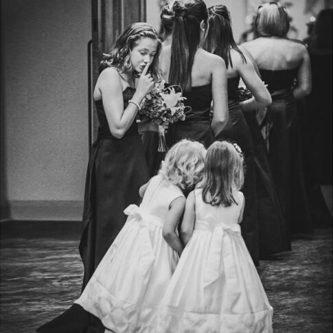 A bridesmaid looks back to gently shush two excited flower girls seconds before they proceed into the chapel.