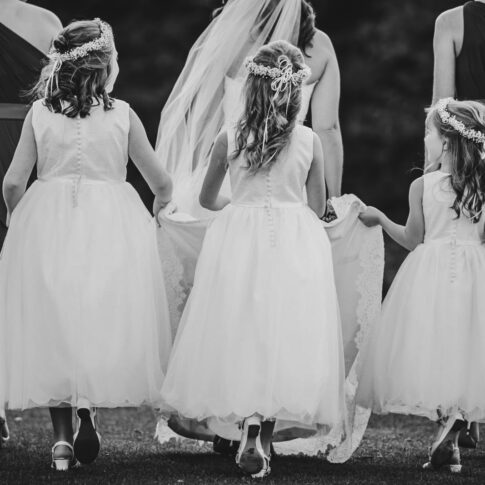 Three flower girls all assist in lifting the brides hem as she walks across grass with her bridesmaids.