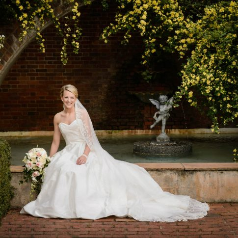 A bride smiles as she is seated on the ledge of a fountain in Furman University's Rose Garden in Greenville, SC.