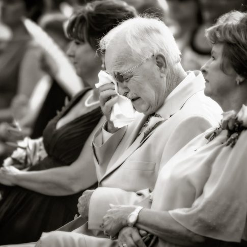 A grandfather takes a moment to dry his tears during the ceremony with his handkerchief.